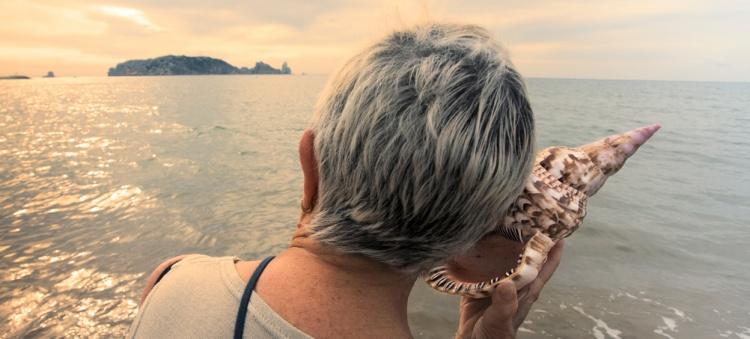 Senior listening to a seashell on the beach